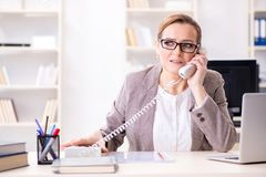 The businesswoman employee talking on the office phone stock images