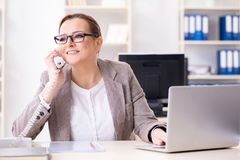 The businesswoman employee talking on the office phone stock photography