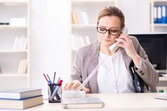 The businesswoman employee talking on the office phone. Businesswoman employee talking on the office phone Stock Image
