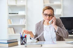 The businesswoman employee talking on the office phone. Businesswoman employee talking on the office phone Royalty Free Stock Image