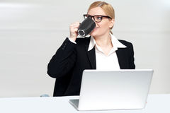 Businesswoman enjoying coffee at work desk Royalty Free Stock Images