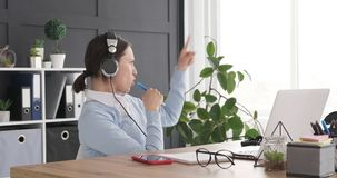 Businesswoman enjoying while listening and singing music at workplace stock footage