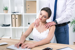 Businesswoman enjoying massage from her colleague while working stock photography