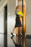 Businesswoman entering office elevator, carrying folders, smiling, side view, surface level Stock Photos