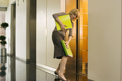 Businesswoman entering office elevator, struggling to keep hold of folders, side view Stock Photos