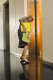 Businesswoman entering office elevator, struggling to keep hold of folders, side view Royalty Free Stock Photos