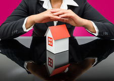 Businesswoman or estate agent and holding a model house Royalty Free Stock Images