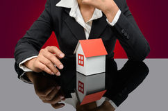 Businesswoman or estate agent and holding a model house Royalty Free Stock Photo