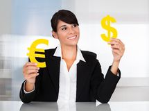 Businesswoman With Euro And Dollar Sign Stock Photography
