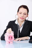 Businesswoman examining her piggy bank. Royalty Free Stock Images