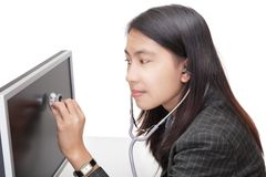 Businesswoman examining PC screen w stethoscope. Young Asian attentive businesswoman examining her PC screen with a stethoscope, sitting at her desk, looking for Stock Image