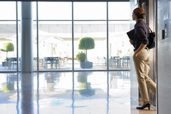 Businesswoman exiting elevator into lobby, carrying shoulder bag and folder, side view Royalty Free Stock Photo