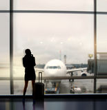 Businesswoman expects fligh. Silhouette of businesswoman which expects flight aboard the plane in airport stock images