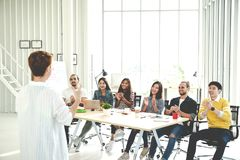 Businesswoman explain ideas to group of creative diverse team at modern office. Rear view of manager gesturing hand standing again. St multiethnic people stock image