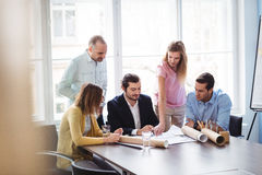 Businesswoman explaining blueprint to colleagues Stock Photography