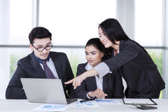 Businesswoman explaining document to partners Royalty Free Stock Photo