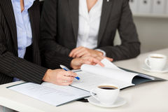 Businesswoman Explaining Documents To Female Coworker At Desk Stock Image