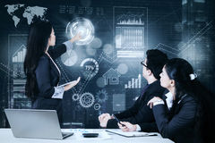 Businesswoman explaining growth graph to her colleague Stock Photo