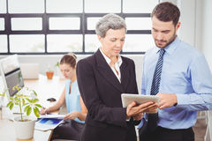 Businesswoman explaining male colleague over digital tablet. While standing in office Royalty Free Stock Image