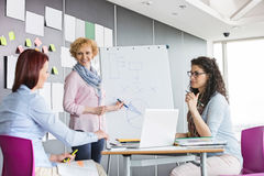 Businesswoman explaining pie chart to colleagues in creative office Stock Photography