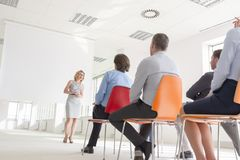 Businesswoman explaining strategy to colleagues during meeting at office stock photo