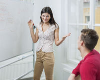 Businesswoman explaining strategy to coworker in office Royalty Free Stock Photography