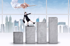 Businesswoman exploitation concept. Female entrepreneur tied on ropes and walk on business graph with controlled by someone Stock Photos