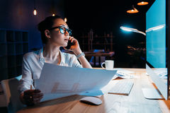 Businesswoman in eyeglasses holding blueprint and talking on smartphone Stock Photos