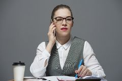 A businesswoman in eyeglasses making a call. Apretty young brunette businesswoman in eyeglasses dressed in a white blouse and grey jacket having a call drinking stock photo