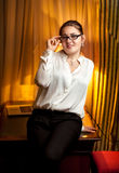 Businesswoman in eyeglasses sitting on table Stock Images