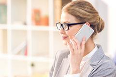 Businesswoman with eyeglasses using smartphone working in office Stock Photos