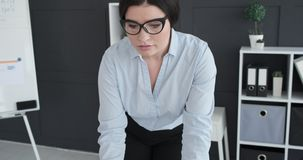 Businesswoman in eyeglasses working at office. Young businesswoman working at office stock footage