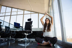 Businesswoman with eyes closed doing yoga on floor stock images