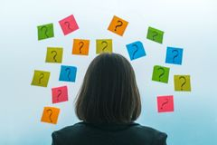 Businesswoman facing questions and challenges. In business situation, rear view of female business person looking at question marks written on colorful sticky stock photos