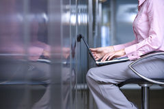 Businesswoman facing wall, laptop computer on lap, mid section, side view Stock Photography