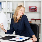 Businesswoman Fanning Herself With Documents At Desk Stock Images