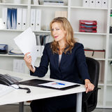 Businesswoman Fanning Herself With Documents Stock Photography
