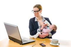 Businesswoman feeding baby Royalty Free Stock Photography