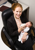 Businesswoman feeding baby at desk Stock Photo