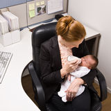 Businesswoman feeding baby at desk Royalty Free Stock Photos