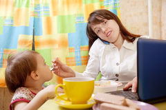 Businesswoman feeding baby and  using  latop Royalty Free Stock Images
