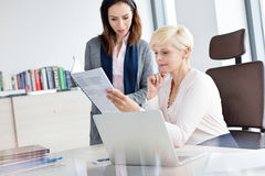 Businesswoman with female manager reading book at desk in office Royalty Free Stock Images