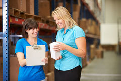 Businesswoman And Female Worker In Distribution Warehouse. Smiling at each other stock image
