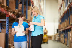 Businesswoman And Female Worker In Distribution Warehouse. Talking stock photo