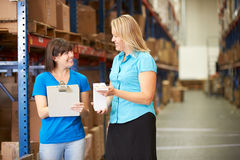 Businesswoman And Female Worker In Distribution Warehouse. Talking royalty free stock photography
