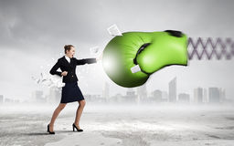 Businesswoman fighting with boxing glove. Boxing glove on spring striking businesswoman down Royalty Free Stock Photography