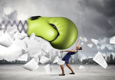 Businesswoman fighting with boxing glove. Boxing glove on spring striking businesswoman down Stock Images