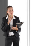 Businesswoman with file. Smart, attractive  businesswoman with folder and pen looking puzzled and standing in front of window Royalty Free Stock Photo
