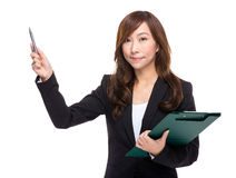 Businesswoman with file pad and pen indicate something Royalty Free Stock Photo