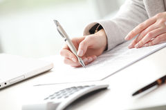 Businesswoman fill the form. Businesswoman sitting at desk and fill the form stock photography